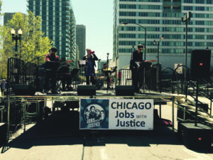 Local 10-208 members took part in a May Day rally held in Chicago's Haymarket Square. On stage (L to R) are: Chris Clemente (bass), Vijay Tellis-Nayak (keyboard), Angie Pope (vocals), Dan Leali (drums), and Mike Pinto (guitar, band leader).